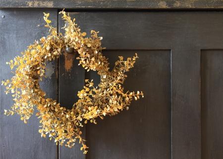 door knob: Yellow wreath hanging on vintage wooden door.