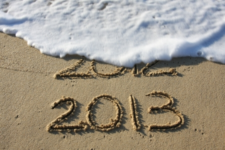 2013 written in the sand with 2012 washed away by the surf   photo