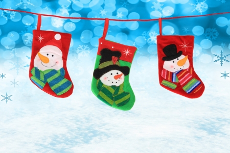 Three hanging Christmas snowman stockings on a snow background   photo