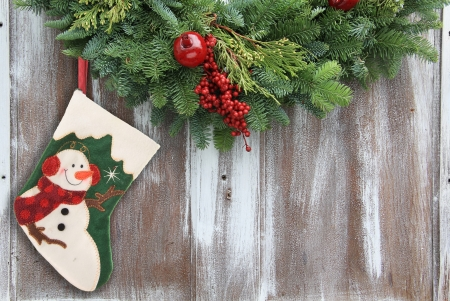 Christmas garland with a snowman stocking on a rustic wooden background. photo