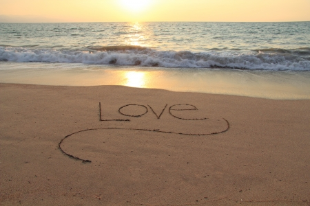 The word Love, handwritten in a sandy beach at sunset   photo