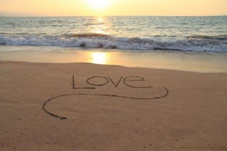 destination wedding: The word Love, handwritten in a sandy beach at sunset