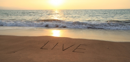 The word Live hand written in the sand at sunset   photo