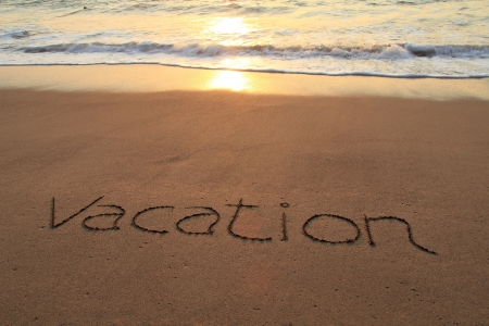 Vacation written in the sand on a sunset beach   photo