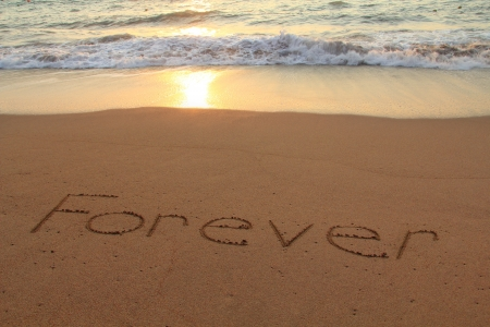 Forever written in the sand on a beach at sunset   photo