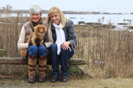 Mother and daughter outside with a dachshund puppy   Stock Photo - 17855852