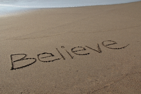 believe: Believe escrito en la arena en la playa