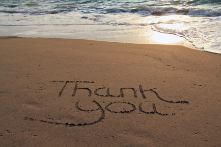 Thank you written in the sand on the beach