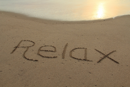 The word relax hand written in the sand at sunset Stock Photo - 17960047