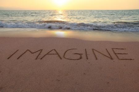 Imagine written in the sand on a sunset beach   Foto de archivo
