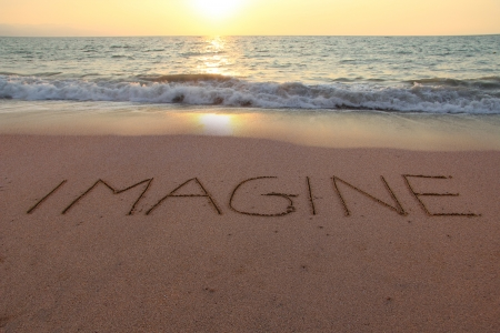 Imagine written in the sand on a sunset beach   Stock Photo