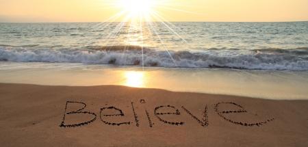 creer: Believe escrito en la arena en la playa