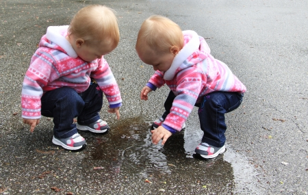 twins: One year old twin girls playing with a puddle of water   Stock Photo