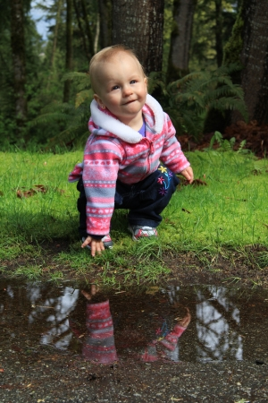 One year old girl outside, playing with a puddle Stock Photo - 19090768