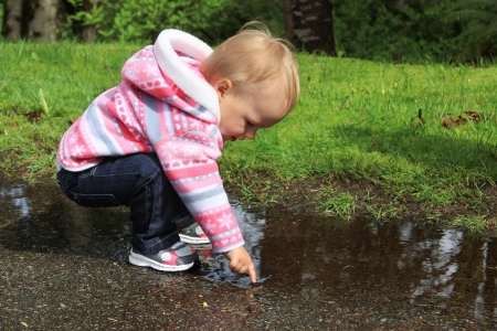 One year old little girl playing in a water puddle Stock Photo - 19126477