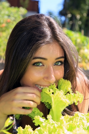 Beautiful smiling young woman with long dark hair outside eating fresh lettuce   photo
