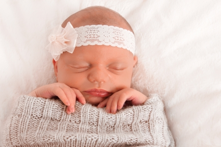 Newborn baby asleep on a blanket photo