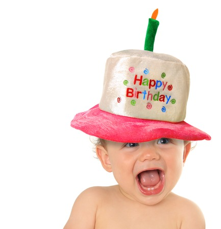 Smiling baby wearing a Happy Birthday hat