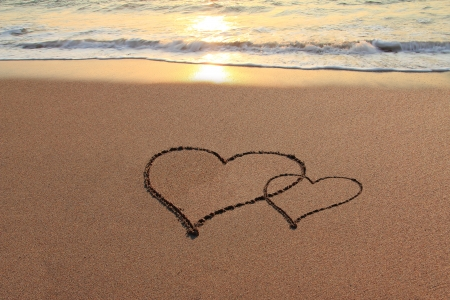 Hearts in the sand on the beach at sunset   photo