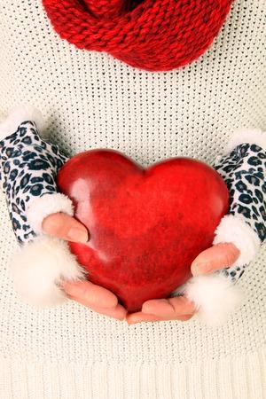 el coraz�n de san valent�n: Cerca de la mujer en invierno su�ter, bufanda y guantes, sosteniendo un coraz�n de San Valent�n