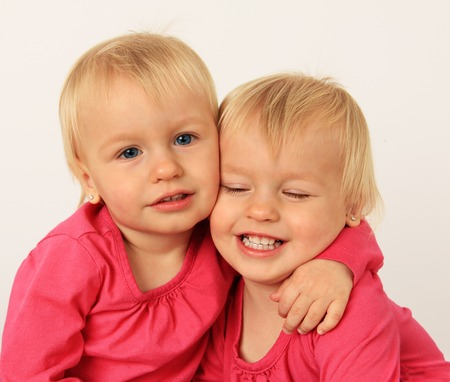Cute two year old identical twin girls hugging   photo