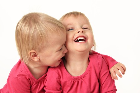 Cute two year old identical twin girls laughing photo