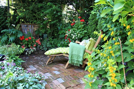 Comfortable lounge chair in a small private garden  Also available in vertical