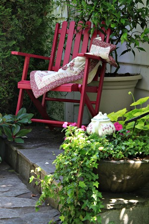 vertical garden: Colorful rocking chair in a cottage garden setting.