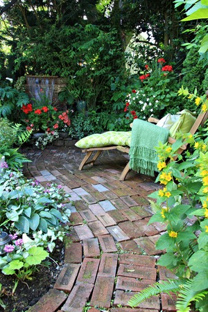 water feature: Comfortable lounge chair in a small private garden. Also available in horizontal.  Stock Photo