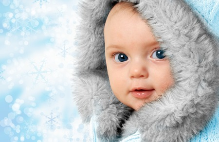 parka: Beautiful baby girl on a snow flake background wearing a winter fur coat. Stock Photo