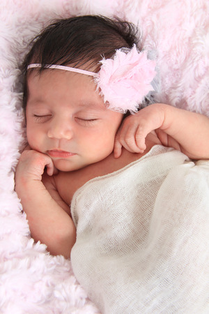 Newborn baby girl of Caucasian and Asian heritage, wearing a head band. photo