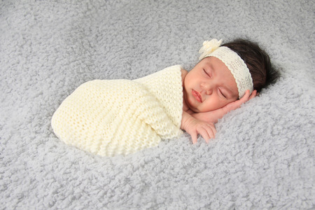 Newborn baby girl of Caucasian and Asian heritage, wearing a lace head band.
