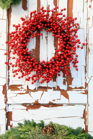 Christmas wreath of  evergreen and red holly berries against a vintage wooden door. Banco de Imagens
