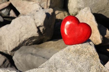 valentijn hart: Red Valentine hart in evenwicht op grote rotsen. Stockfoto