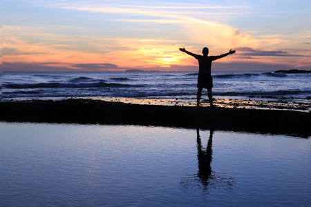 alabando a dios: Silueta de un hombre con los brazos extendidos al atardecer en una playa. Foto de archivo