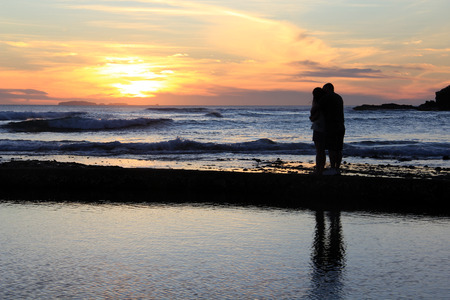 romantic room: couple hugging and watching the sunset. Stock Photo