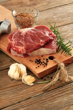 Raw prime rib beef steaks with spices, garlic and rosemary. Also available in horizontal. photo