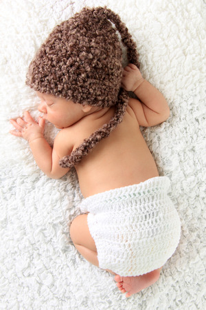 diaper baby: Newborn baby wearing a knitted hat and knitted diaper cover.