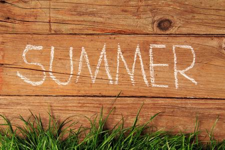 Summer written in chalk on a wooden fence. photo