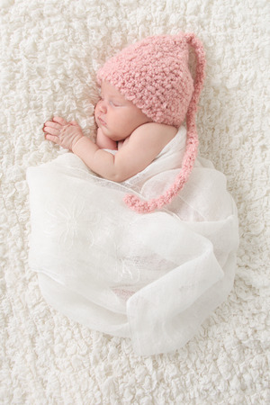 Newborn baby girl wrapped in vintage lace, wearing a pink knitted hat.