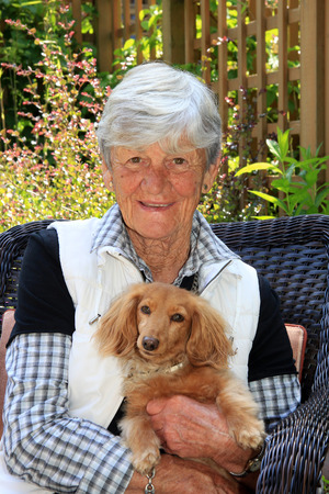 Smiling senior lady age 75,  in the garden with her dachshund dog.