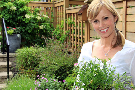 Smiling fifty year old lady gardener outside in the garden holding a pack of lobelia. photo