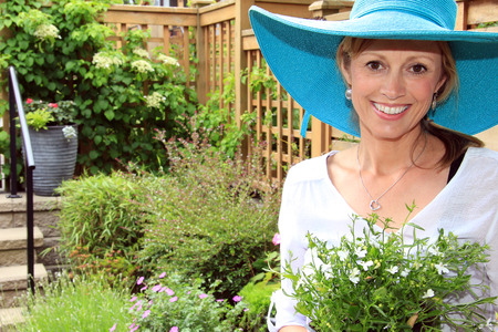 lobelia: Smiling fifty year old lady gardener outside in the garden holding a pack of lobelia. Stock Photo
