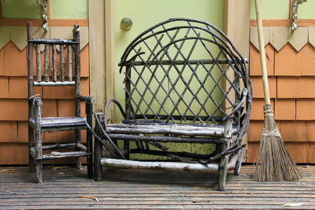 loveseat: Small child size chair and loveseat made from tree branches on an wood porch.
