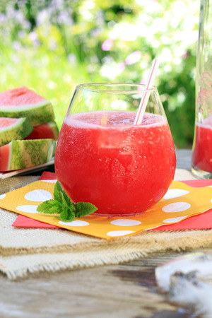 Watermelon drinks outside in the garden with straws and fresh mint. Also available in horizontal. Imagens