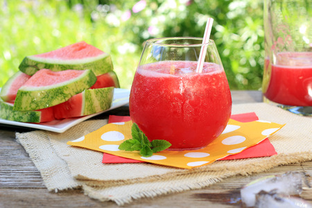 field glass: Watermelon drinks outside in the garden with straws and fresh mint. Also available in vertical. Stock Photo