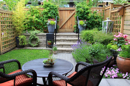 Small townhome garden with patio furniture amidst blooming lavender. photo
