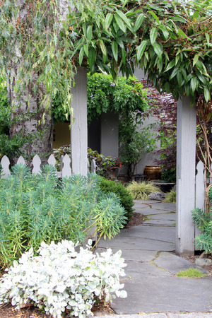 perennials: Garden entrance and picket fence surrounded by lush perennials. Also available in horizontal.