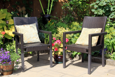 Two garden chairs surrounded by shrubs and flowers.