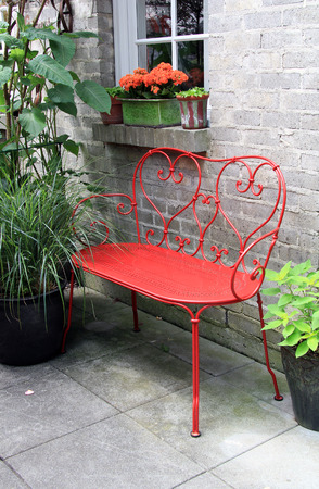 loveseat: Red wrought iron bench outside on a garden patio. Stock Photo